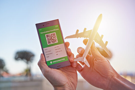 Smartphone displaying on app mobile valid digital green vaccination certificate for Covid-19 and airplane toy in hand. Immunity vaccine e-passport, vaccination certificate, health passport for travel