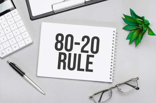 Writing text showing The 80 on 20 Rule. Calculator,pen,plan,glasses and black folder on grey background