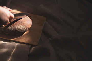 Hands holds a freshly baked loaf of rye bread and begins to cut a piece from it on a wooden board in the shade in the rays of the. Bakery products and baking bread at home