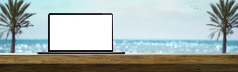 laptop on a table on a sunny day in the summer with beach in the background