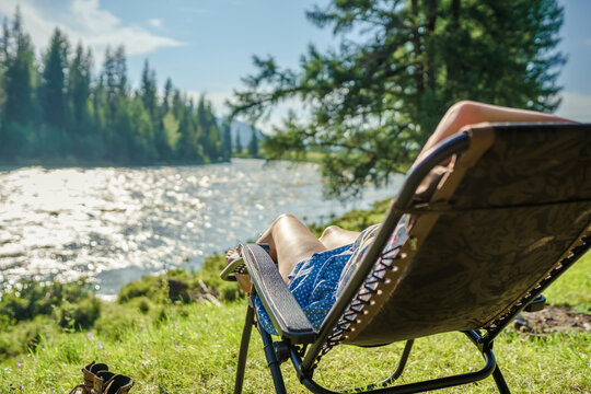 one person relaxing in the camping chair on the beach of river