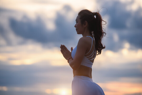 Asian young woman practicing easy yoga poses for beginners. Exercise while looking out to the sky in sunset. Meditation and Strengthening Exercises with yoga.