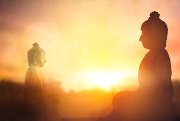 Vesak Day concept: Silhouette Buddha on golden sunset background