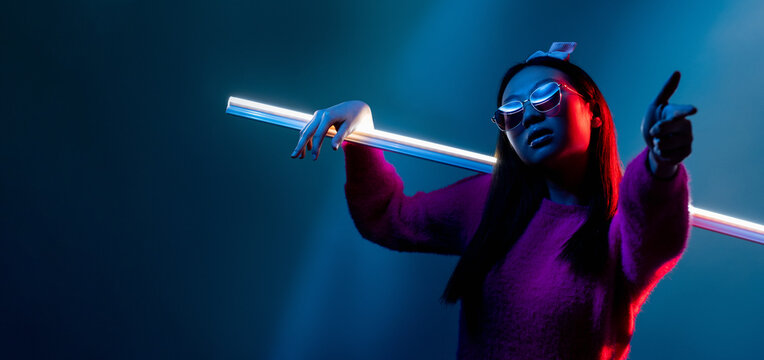 Bad girl. Cyberpunk portrait. Night subculture. Blue red neon light cool Asian woman in pink in sunglasses with showing finger gun gesture isolated on dark copy space background.