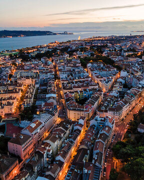 Aerial view of Alcantara residential district of Lisbon with Tagus river in background at sunset, view of city skyline illuminated, Lisbon, Portugal.