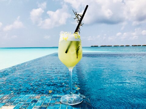 View Of Yellow Cocktail In Swimming Pool In Front Of The Ocean