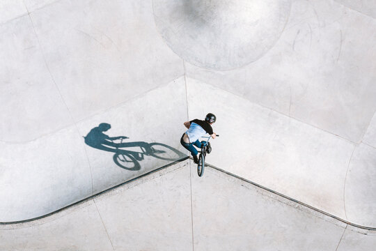 Aerial view of BMX bike rider doing turn down trick in local skatepark in Panevezys, Lithuania.