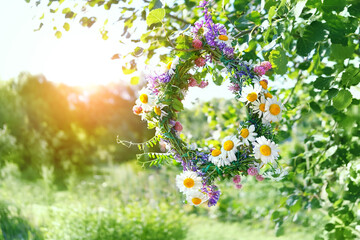 wreath of Meadow flowers in garden. beautiful summer season. Summer Solstice Day, Midsummer concept. floral traditional decor. pagan witch traditions, wiccan symbol and rituals