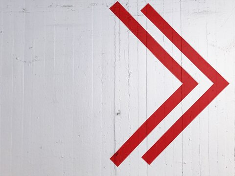 Red Arrow Symbol On White Wall