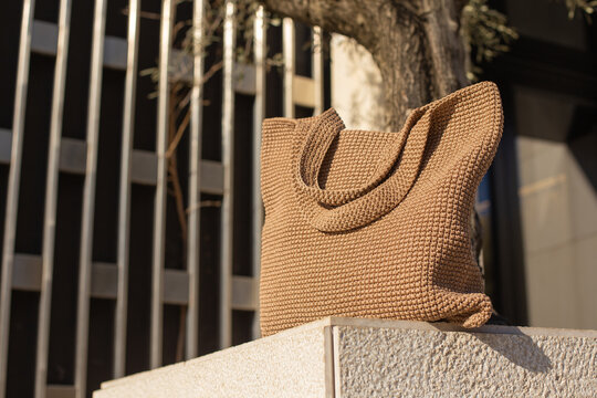 Brown knitted handmade bag on light stone pedestal on the street. Hero view. Eco-friendly shopping. Zero waste lifestyle.