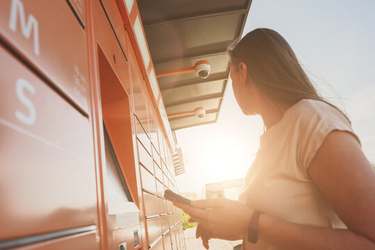 Woman picks up mail from automated self-service post terminal machine.