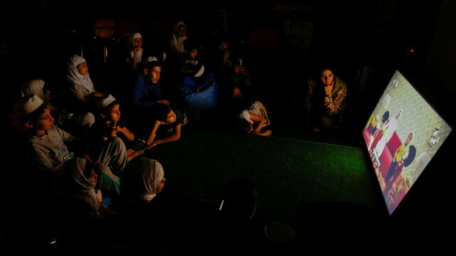 Iraqi single mother Marwa Raed Taha, who works as a volunteer, sits with a group of children watching television, at the Amiriya shelter in Baghdad