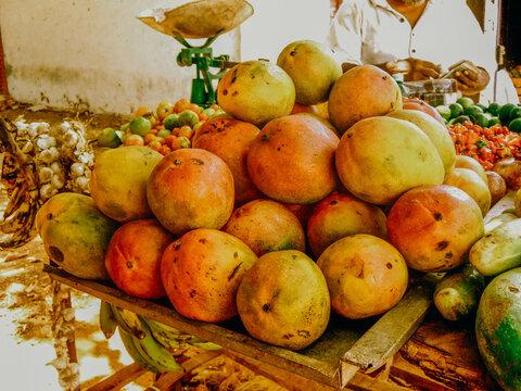Pile of yellow mangos on market table