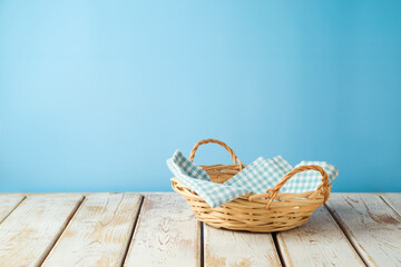 Obraz Empty wicker basket with tablecloth on rustic table over blue wall  background.  Kitchen mock up for design and product display. - fototapety do salonu