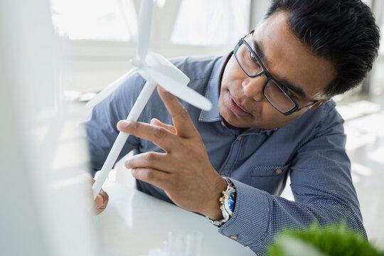 Serious scientist examining wind turbine model