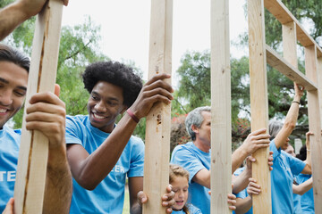 Group of volunteers holding wooden frame at park