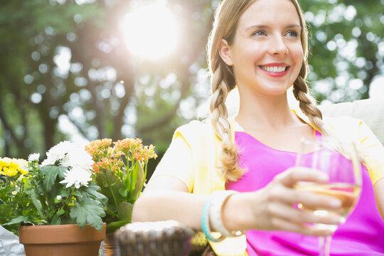 Beautiful woman holding wineglass in yard