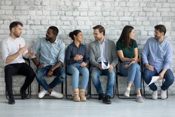 Obraz Confident motivated diverse job candidates and competitors making friends in queue, enjoying friendly talk, discussing resumes and hiring, waiting for job interview at employers HR recruiter office. - fototapety do salonu