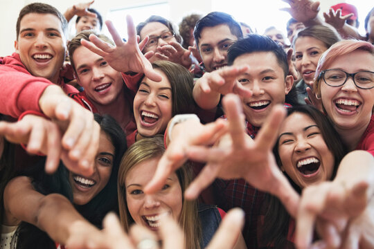 Portrait of large group of students cheering at college sporting event