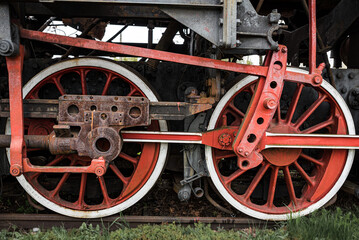 The wheels of an old vintage locomotive repainted in red and white