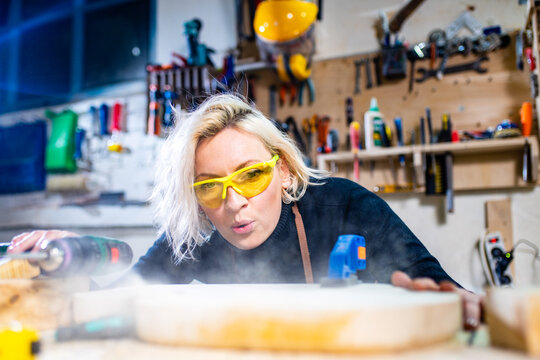blonde female carpenter using tools for her work in a woodshop