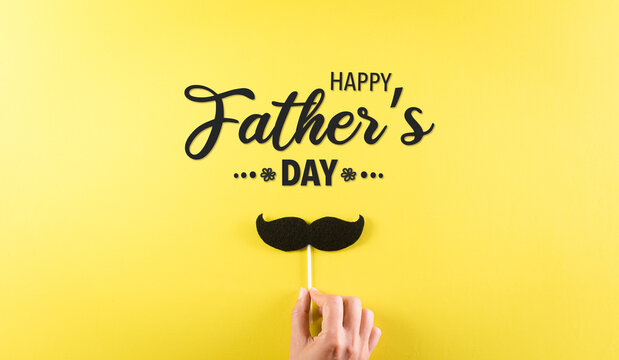 Happy Father's Day background concept with hand holding black mustache with the text on pastel yellow background.