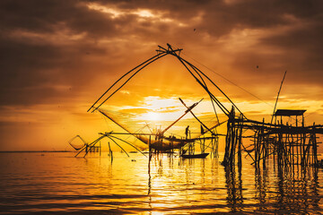 silhouette scenery of sunrise at pakpra phatthalung with thai traditional fishing trap