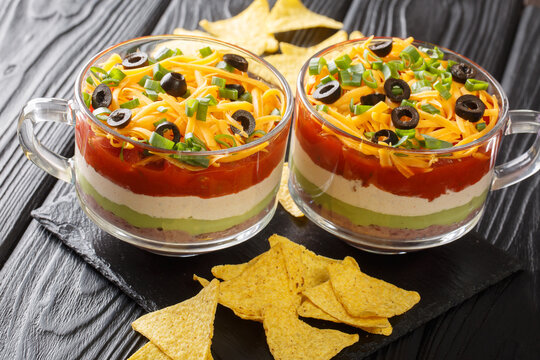 Delicious food appetizer Mexican seven-layer dip salad served with chips close-up on the table. horizontal