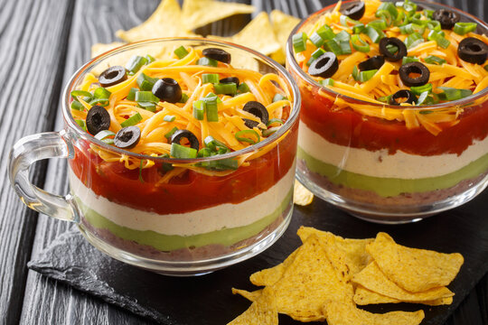 Classic Mexican 7 Layer Dip with corn chips close up in the glass on the table. Horizontal