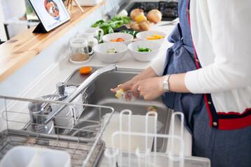 Fototapeta タブレットを見ながら自宅のキッチンで料理をする主婦 obraz
