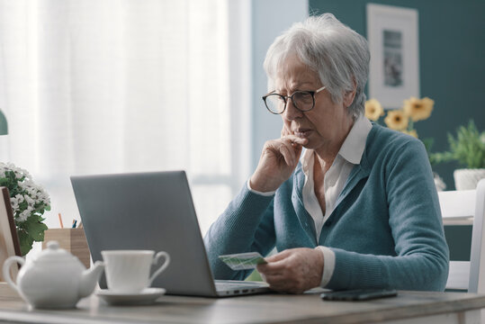Confused senior woman using her credit card online