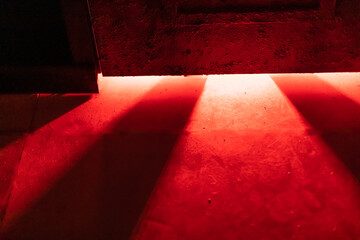 Obraz A mystical and dangerous red light through a gap under the door. Fabulous atmosphere of mysteries and horrors for decor - fototapety do salonu
