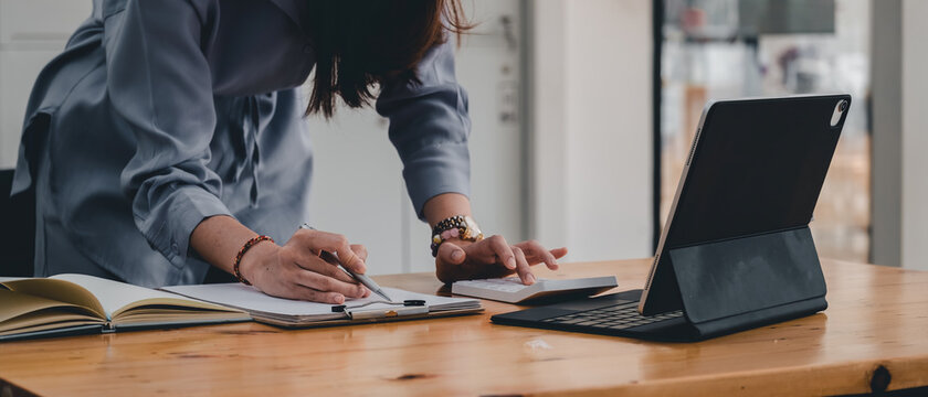 businesswoman or accountant taking note and working on calculator and laptop computer to calculate business data during make note at notepad, accountancy document at office