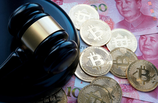 Bitcoin in China concept. Bitcoin coins placed on Yuan banknotes. Ban of Bitcoin in Republic of China.