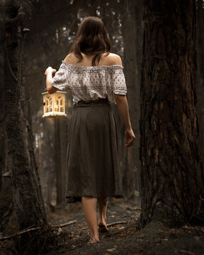 young woman with lantern in the dark forest