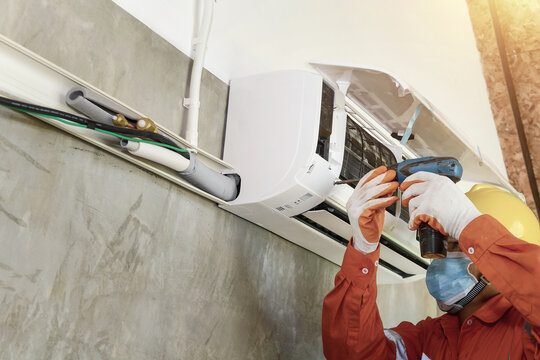 A young Asian air conditioner technician or air-conditioning installation technician is about to repair air conditioning in homes and buildings