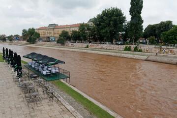 Fototapeta Puste nabrzeże błotnistej rzeki z pustą restauracją obraz