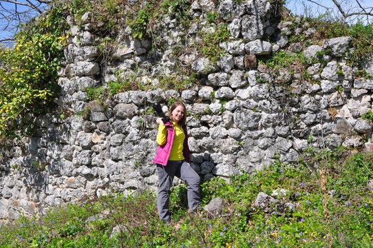 A woman with a camera stands near the destroyed fortress wall