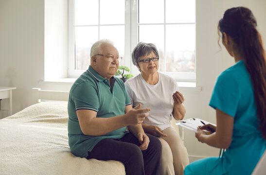 Worried married senior couple sitting on bed and talking to nurse, family physician or general practitioner. Doctor listening to elderly patients during home visit or interview in retirement home