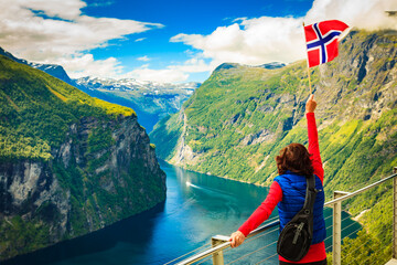 Tourist over Geirangerfjord with norwegian flag