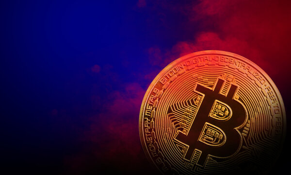 golden bitcoin coin is in red and blue smoke background. cryptocurrency concept
