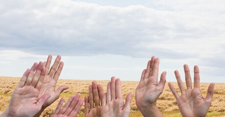 Composition of hands held up against countryside field and clouds