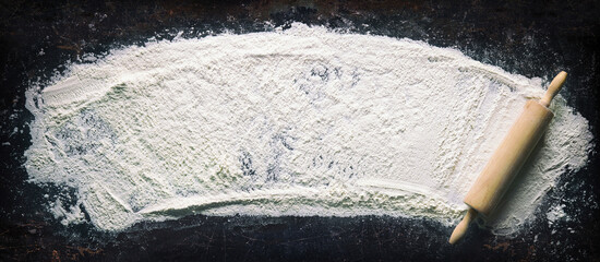 Abstract baking background with the rolling pin and flour on dark table