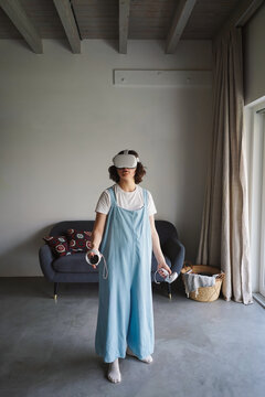 Female in modern VR goggles and with controllers standing in room at home and playing videogame in cyberspace