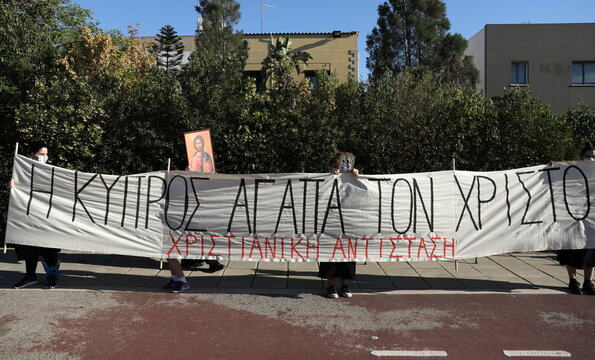 """People hold a banner reading """"Cyprus loves Christ"""" during a protest against the song """"El Diablo"""", Cyprus pick to represent the island  at the annual Eurovision Song Contest outside the offices of the Cyprus Broadcasting Corporation in Nicosia"""