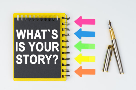 On a white background lies a pen, arrows and a notebook with the inscription - WHATS IS YOUR STORY