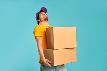 Fototapeta Young bearded courier delivery man in uniform holding heavy boxes isolated on blue background. Home delivery. obraz