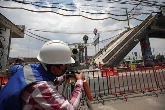 A topographer works as part of the investigations in front of the site where an overpass for a metro partially collapsed with train cars on it, in Mexico City