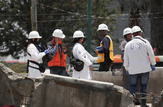 Employees from Mexico's Attorney General of Justice work as part of the investigations at the site where an overpass for a metro partially collapsed with train cars on it, in Mexico City