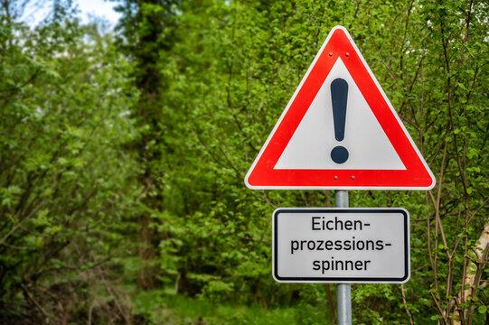 Warnschild in einem Waldgebiet vor dem Eichenprozessionsspinner und dessen gesundheitlichen Auswirkungen
